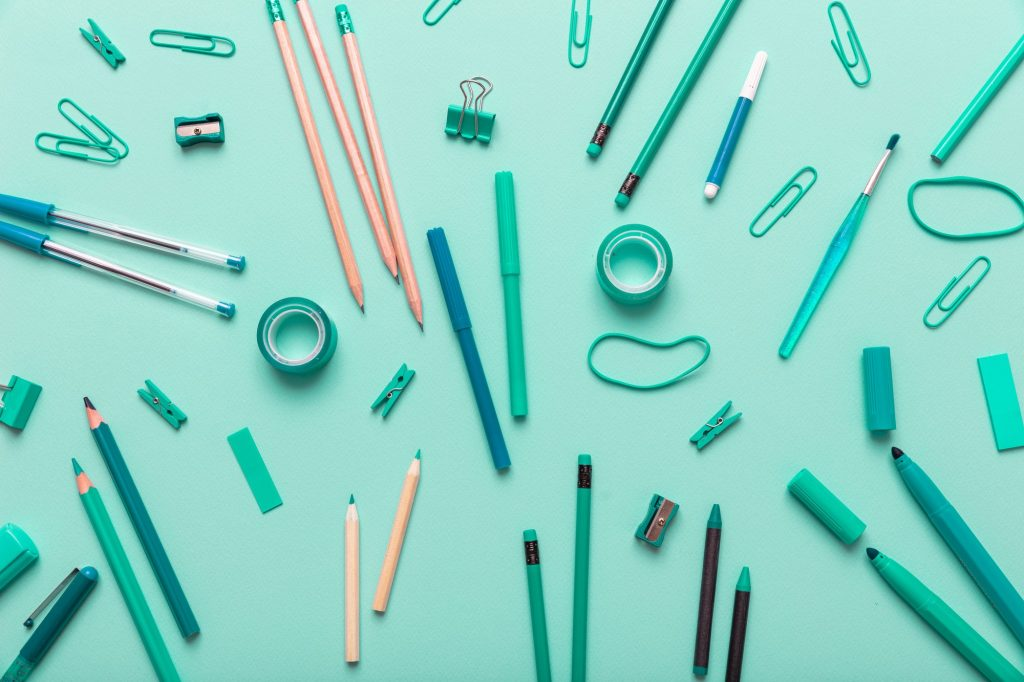 Flat lay of office, school stationery on green background